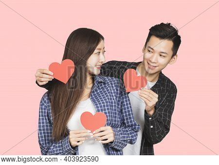 Young Couple Showing Red Hearts And Standing Over Pink Background