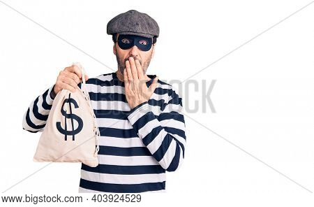 Middle age handsome man wearing burglar mask holding money bag covering mouth with hand, shocked and afraid for mistake. surprised expression