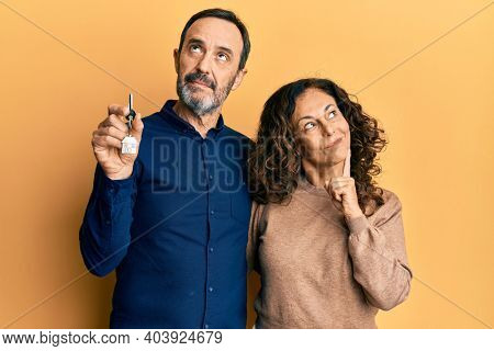 Middle age hispanic couple holding keys of new home serious face thinking about question with hand on chin, thoughtful about confusing idea