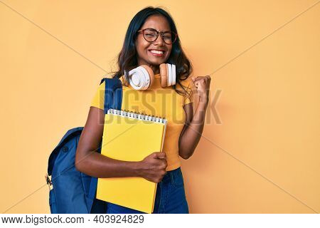 Young indian girl holding student backpack and books screaming proud, celebrating victory and success very excited with raised arm