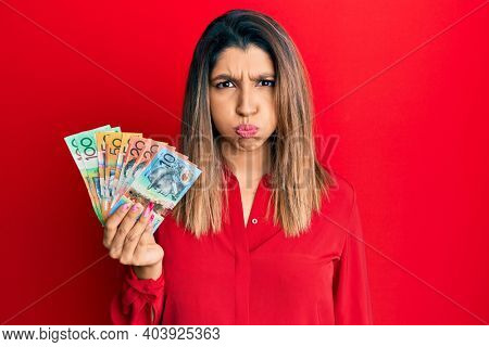 Beautiful brunette woman holding australian dollars puffing cheeks with funny face. mouth inflated with air, crazy expression.