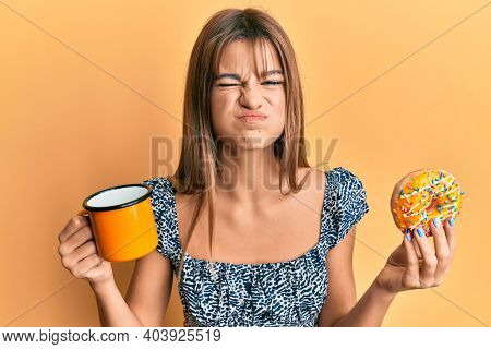 Teenager caucasian girl eating doughnut and drinking coffee puffing cheeks with funny face. mouth inflated with air, catching air.