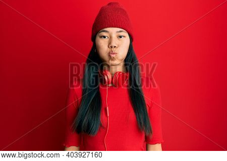 Young chinese woman listening to music using headphones puffing cheeks with funny face. mouth inflated with air, crazy expression.