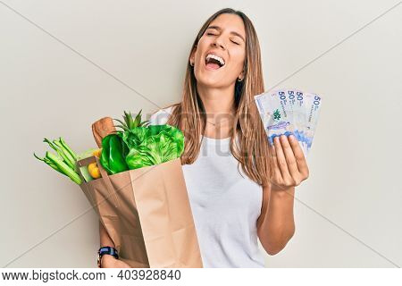 Brunette young woman holding groceries and 50 colombian pesos banknotes smiling and laughing hard out loud because funny crazy joke.