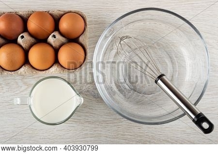 Cardboard Box With Brown Chicken Eggs, Jug Of Milk, Whisk In Transparent Bowl On Wooden Table. Top V