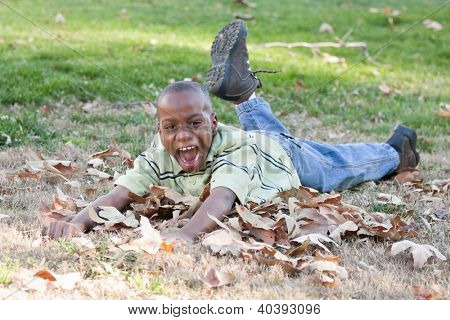 Young Handsome African American Boy Playing in the Park Among the Leaves.
