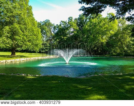 A Fountain In A Pond In The Summer.