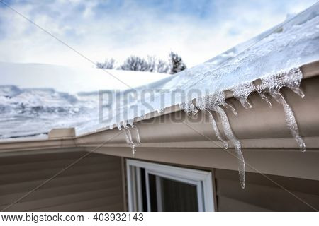 Ice dam in gutter and ice frozen on roof in winter, shallow focus on icicles in foreground