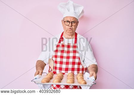 Senior grey-haired man wearing baker uniform holding homemade bread puffing cheeks with funny face. mouth inflated with air, catching air.