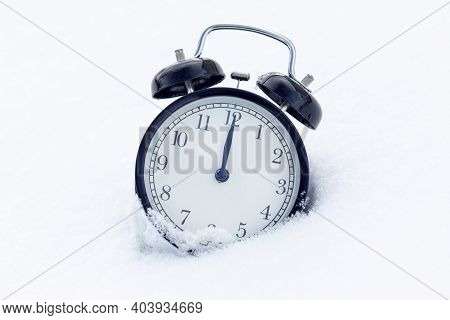A Classic Black Alarm Clock In The Snow. New Year Concept. The Time Is 12 O'clock On The Clock.