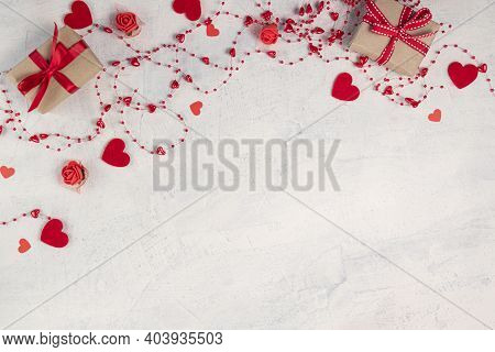Two Gifts With Red Ribbon And Red Beads With Hearts On White Stone Background.valentine's Day Backgr