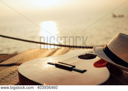 Guitar And Hat On Reed Mat Near The Sea At Sunset. Travel, Vocation, Holiday, Summer Concept.