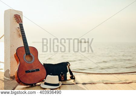 Hat, Bag And Guitar On Reed Mat Near The Sea At Sunset. Travel, Vocation, Holiday, Summer Concept.