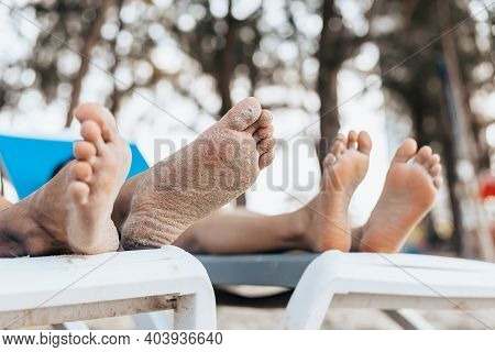 Foot Of Couple Of Lovers Sitting On Beach Chair On The Beach In The Morning.  Newlywed Couple On A R