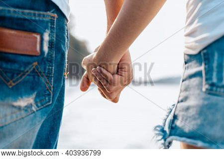 Couple Of Lovers Holding Hands On The Beach In The Morning.  Newlywed Couple On A Romantic Vacation