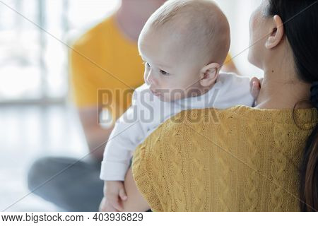 Happy Mother, Father With Baby Playing Together At Home. Mother Hug Baby.