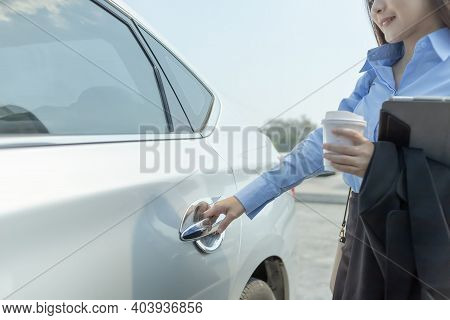 Hand Of  Businesswoman Opening A Car Door And Left Hand Hold Cup Of Coffee And Tablet.