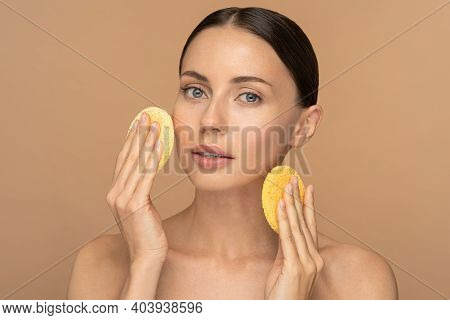 Perfect Young Woman With Nude Make-up And Naked Shoulders Cleaning Her Face With Exfoliating Sponge,