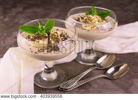 Two Tender Banana Mousses Decorated With Mint And Chocolate Chips.