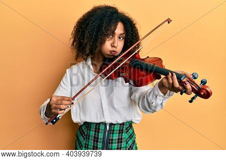 Beautiful african american woman with afro hair playing classical violin puffing cheeks with funny face. mouth inflated with air, catching air.