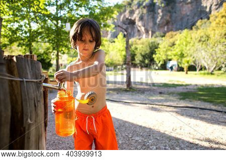 A Child Pours Water From A Tap Into A Refillable Bottle. The Boy Quenches Thirst On A Hot Summer Day