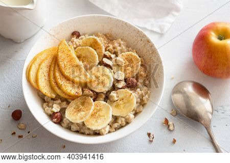 Delicious Healthy Breakfast. Oatmeal With Banana, Apple, Nuts And Cinnamon On A Light Gray Backgroun