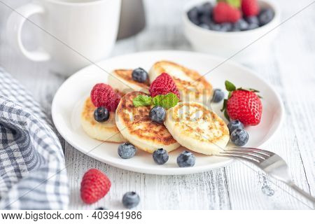 Cottage Cheese Pancakes With Fresh Berries On White Wooden Table. Tasty Breakfast Food. Syrniki - Im