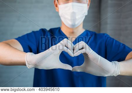 Close Up Of Medical Doctor Making A Heart Symbol Shape Hands Gesture With Copy Space. Medical Worker