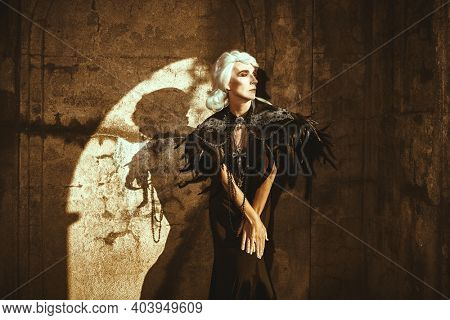 Portrait of an aristocratic old widow woman in a rich black dress standing sad by the ruined wall and looking to the window. Black Widow. Fantasy World. Halloween.