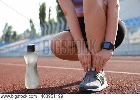 Woman With Fitness Tracker Tying Shoelaces At Stadium, Closeup