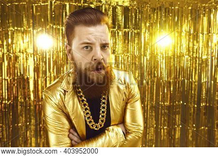 Man In Extravagant Golden Jacket With Gold Chain Around Neck Looking At Camera With Mistrust