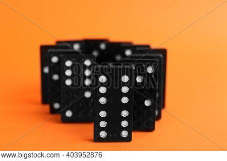 Black Domino Tiles With White Pips On Orange Background