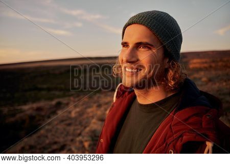 Portrait Of Happy Male Wearing Cap Smiling With Sunrays Falling On Face While Looking Away