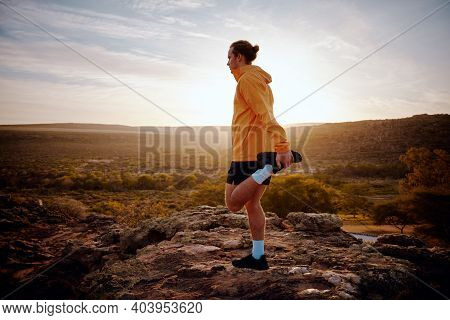 Male Athlete Doing Leg Stretching Exercise Preparing For Run In Nature Trail At Morning With Sunrise