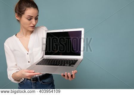 Beautiful Amazed Young Woman Holding Netbook Computer Looking At Display Wearing White Shirt Isolate