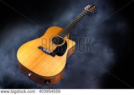 Acoustic Classical Yellow Six-string Guitar With Black Pickguard In Smoke On Black Isolated Backgrou
