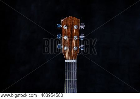 Acoustic Guitar Head With Chrome Tuning Pegs And Fretboard On Isolated Black Background