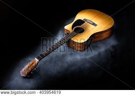Acoustic Six-string Guitar Of Classic Yellow Color On Isolated Black Background Surrounded By Fog