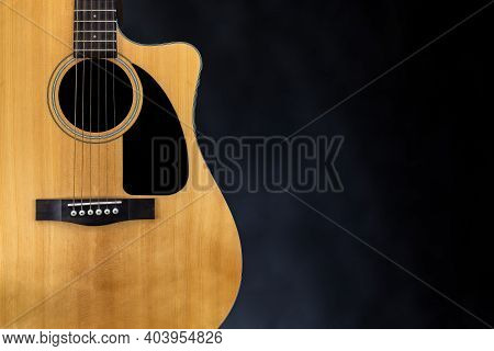 Sound Board Of Classic Yellow Acoustic Guitar With Black Pickguard And Strings Near Isolated Black B