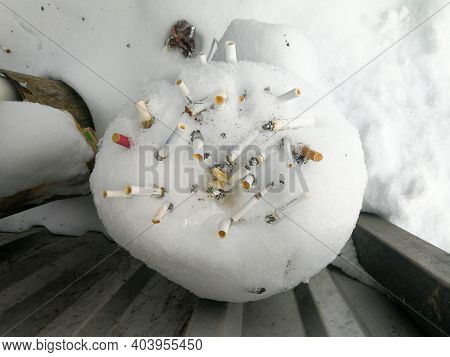 Moscow. Russia. January 19, 2021. Many Cigarette Butts Stick Out In The Snow In The Trash Can. The B