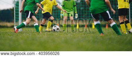 Horizontal Image Of Kids Playing Football. Happy Boys Kicking Classic Soccer Ball On Grass Field. Sc