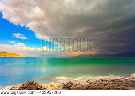 Israel. The picturesque and magnificent Dead Sea. Winter thunderstorm begins. Low winter clouds are reflected in the green sea water. The healing waters of the Dead Sea