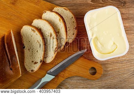 Slices Of Bread With Raisin, Kitchen Knife On Bamboo Cutting Board, Plastic Box With Creamy Cheese O