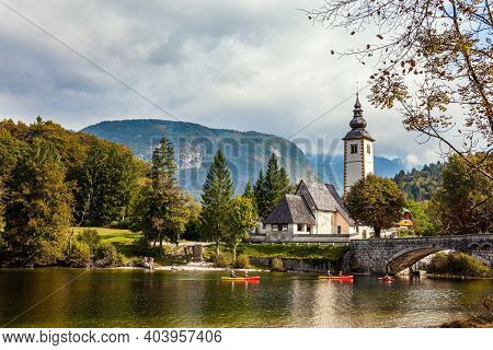 Magnificent alpine lake of glacial origin in the Julian Alps. Picturesque shores of Lake Bohinj. Slender bell tower and a snow-white church. Slovenia, Central Europe