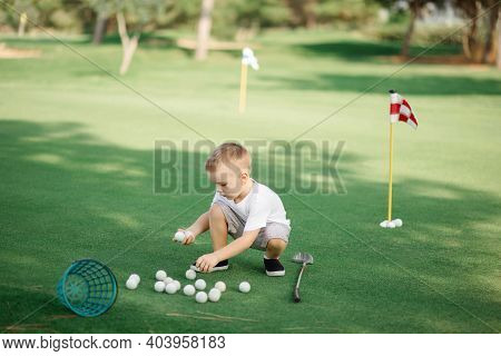 Little Boy Golfer With His Plastic Golf Set On Green Field Outdoor, Collecting His Golf Balls In Bas