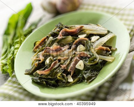 boiled swiss chard salad with anchovy and garlic, selective focus