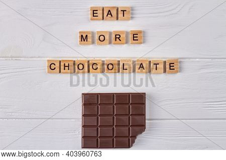 Eat More Chocolate Concept. Dark Chocolate Bar On White Wood.