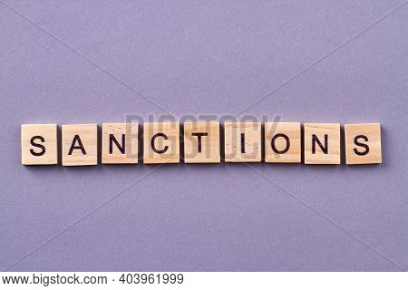 Sanctions Word Made Of Wooden Cubes. Isolated On Purple Background.