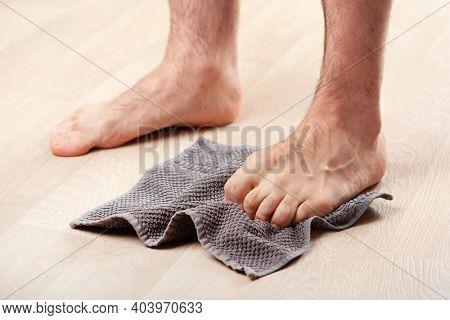 man doing flatfoot correction gymnastic exercise grabbing towel at home