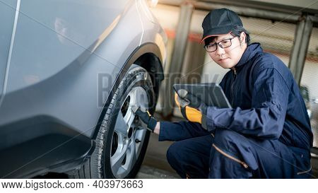 Asian Auto Mechanic Holding Digital Tablet Checking Car Wheel And Tire In Auto Service Garage. Mecha